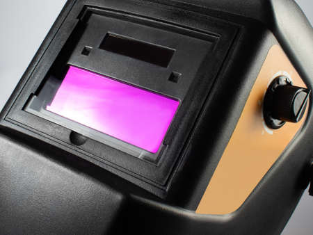 Photo of a black welding helmet close-up view on light background.