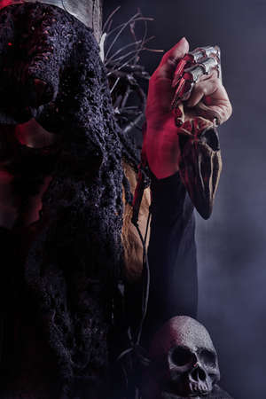 Vertical oriented photo of a female witch queen hand holding wooden bird skull amulet and sitting on a throne made of branches, front close-up view.
