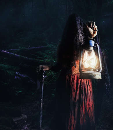 Photo of a female witch holding lantern and cane in dark woods gloomy, scary background.