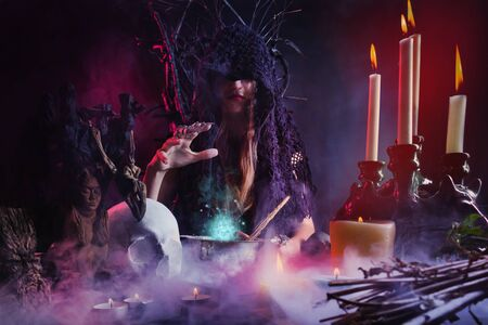 Photo of a female witch sitting at a table full of magic amulets, books and candlestick, casting spell on black and red foggy background.