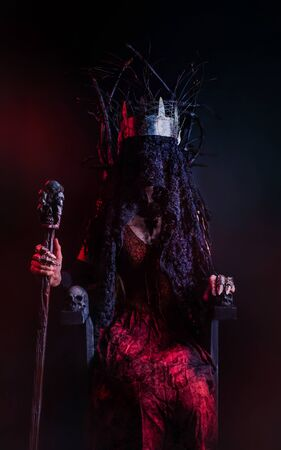 Photo of a female witch queen with metal crown, holding skull cane and sitting on a throne made of branches, front view.