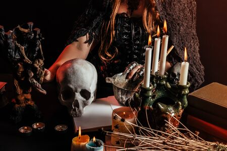 Photo of a female witch sitting at a table with skull, magic amulets and candles.