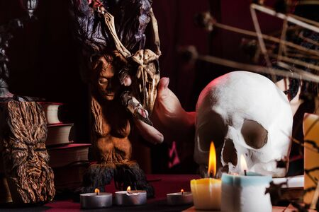 Photo of a female witch hand at a table with skull, magic amulets and candles holding wooden bird skull.