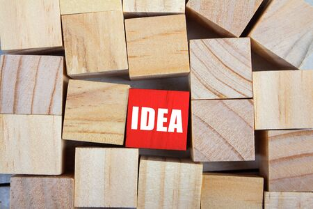 Photo of a pile of different textured wooden cubes and one colored cube with idea sign laying on  table surface.