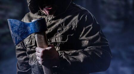 Photo d'un homme tueur en colère effrayant tenant une hache dans un fond de bois brumeux sombre. Banque d'images