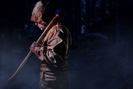Photo of a scary bloody male murderer in brown hood jacket holding an axe in dark woods background, profile view.