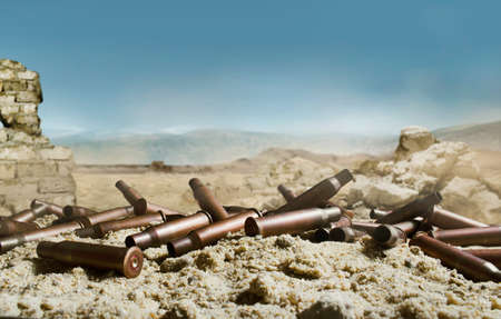 Photo of metal automatic rifle gun shells laying on sand, battlefield background with ruined walls and rocks. Stok Fotoğraf