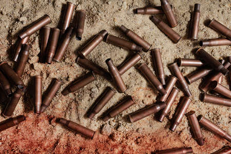 Photo of bloody metal automatic rifle gun shells laying on sand, upper view.