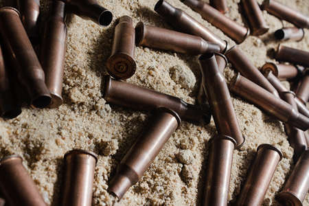 Photo of bloody metal automatic rifle gun shells laying on sand, close-up upper view.