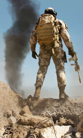 Photo of a fully equipped desert soldier with rifle standing on stone mountain with tactical backpack and smoke on background rear view. Stok Fotoğraf