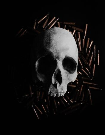 Photo of a human skull laying on a pile of gun shells on black background. Foto de archivo