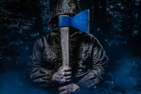 Photo of a scary male in brown hood jacket posing with an axe in dark woods background, front view.