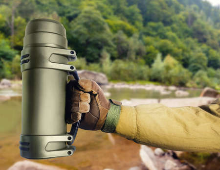 Photo of soldier hand in glove holding tactical flask on nature background.