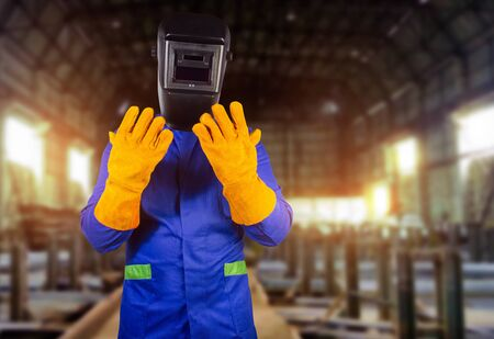 Photo of a fully equipped welder in robe, mask and orange protective gloves standing on steel factory background.