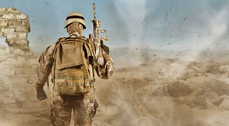 Photo of a fully equipped soldier in uniform, armor, helmet, backpack and rifle standing rear view on desert ruins background with dust flying. Reklamní fotografie
