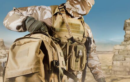 Photo of a fully equipped soldier in uniform, armor and mask walking with backpack in desert battlefield background close-up view.