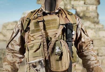 Photo of a fully equipped soldier in uniform, armor, helmet and mask standing in desert battlefield background close-up view. Reklamní fotografie