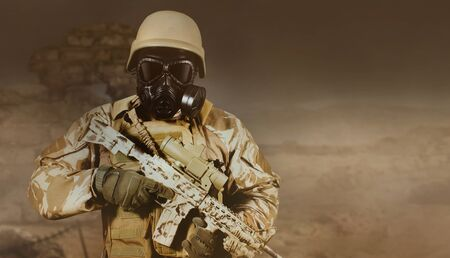 Photo of a fully equipped soldier in uniform, armor, helmet and gas mask standing with rifle in gloomy desert battlefield background. Reklamní fotografie