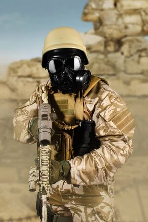 Photo of a fully equipped soldier in uniform, armor, helmet and gas mask attacking with rifle in desert battlefield background.