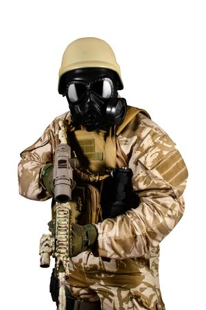 Isolated photo of a fully equipped soldier in uniform, armor, helmet and gas mask attacking with rifle on white background. Reklamní fotografie