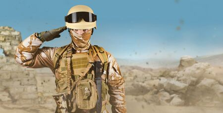 Photo of a fully equipped soldier in uniform, armor, helmet and glasses standing saluting in desert battlefield background.