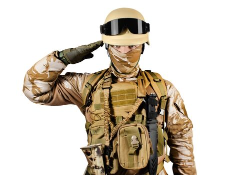 Isolated photo of a fully equipped soldier in uniform, armor, helmet and glasses standing saluting.