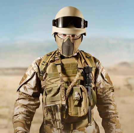 Photo of a fully equipped soldier in uniform, armor, helmet and glasses standing in desert.