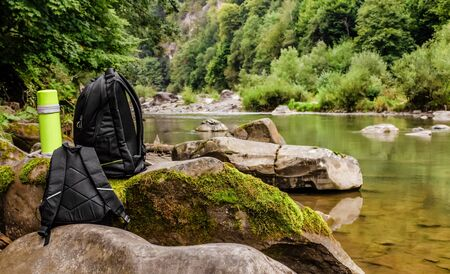 of a travel backpacks with  bottle standing on forest river rocks with stream on background. Reklamní fotografie