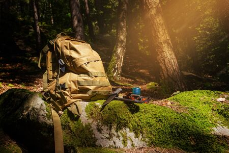 Photo of a tactical olive backpack laying with flashlight and hunting knife on evening forest  rocks with moss.