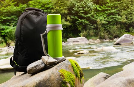 of a travel backpack with  bottle standing on forest river rocks with stream on background. Reklamní fotografie
