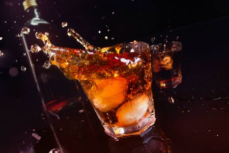 Photo of a whiskey spilling from glasses with ice and bottle on a black background. Reklamní fotografie