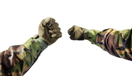 Isolated photo of a first person view soldier fists in tactical gloves and camouflaged tunic on white background.