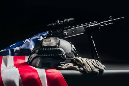 Photo of a black sniper rifle standing on table with soldier helmet with american patch laying on american flag on black background side view. Stock Photo