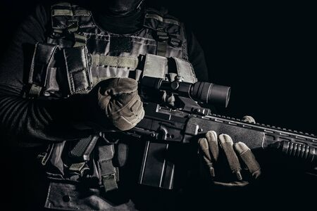 Photo of a soldier in tactical gloves and armor vest standing and reloading sniper rifle on black background.