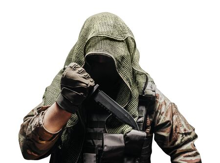 Isolated photo of a fully equipped camouflaged soldier in tectical net scarf with tactical vest and gloves holding knife reverse grip.