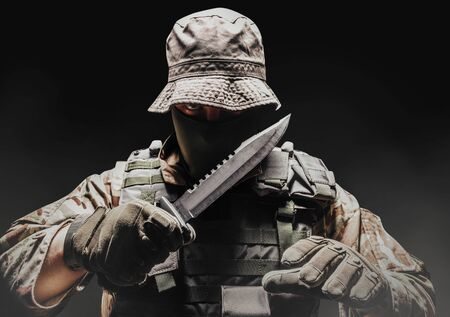 Photo of a fully equipped camouflaged soldier in panama hat with tactical vest and gloves holding knife on dark background wirh fog.