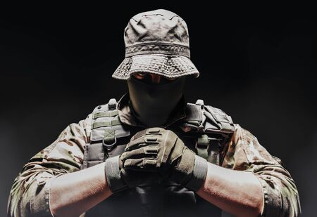 Photo of a fully equipped camouflaged soldier in panama hat posing with fists on dark background wirh fog.