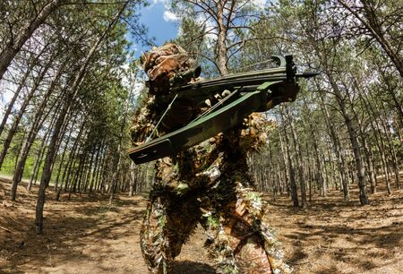 Photo of a camouflaged forest sniper hunter with crossbow posing in woods.