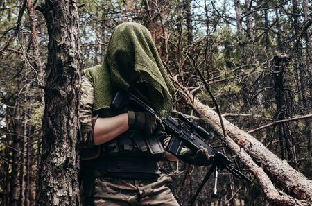 Photo of a fully equipped camouflaged forest sniper with rifle standing in woods closeup.