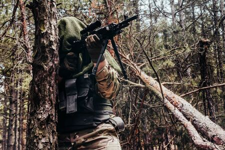 Photo of a fully equipped camouflaged forest sniper with rifle standing and aiming in woods.