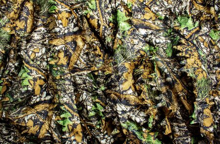 Photo of a hunting forest camouflage textured cloth.