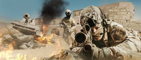 Photo of a fully equipped soldiers laying and aiming rifle on desert battlefield with running soldiers and tank.
