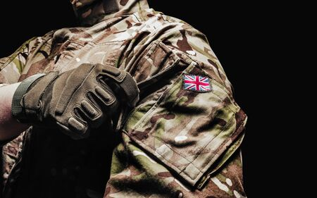 Photo of a british soldier in multicam camouflage tunic using pocket on black background.