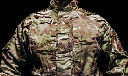 Photo of a soldier in multicam camouflage tunic on black background.