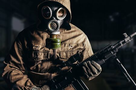 Photo of a stalker man in soviet gas mask holding sniper rifle. Stockfoto