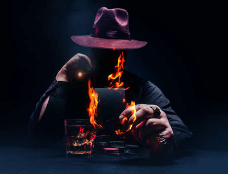 Photo of a demonic gangster with cigar in black shirt and hat playing poker and holding a burning black card.