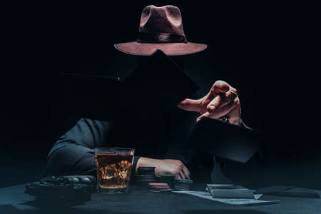 Photo of a shaded gangster in black shirt and hat playing poker and throwing black cards with game chips, revolver gun and money.