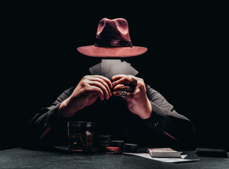 Photo of a shaded gangster in black shirt and hat playing poker and holding black cards with game chips and money. Stockfoto