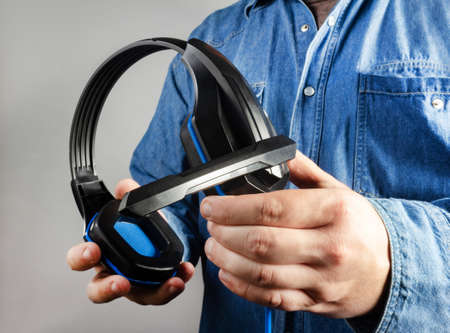 Photo of male hand in shirt holding gaming headphones with microphone closeup view.