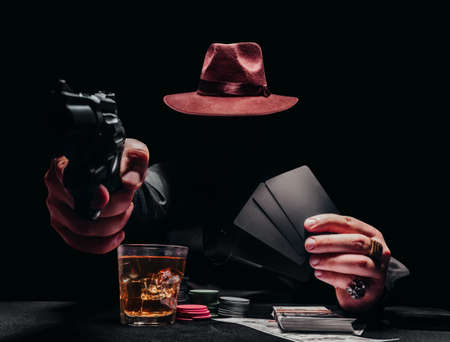 Photo of a shaded gangster pointing gun in black shirt and hat playing poker and holding black cards.